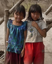 Two smiling girls posing in the Veal Thom village.