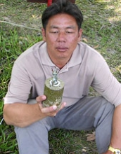 Lim holding a landmine sitting outside the village.