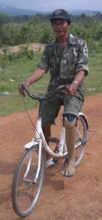 An amputee is able to ride a bicycle with an wooden limb.