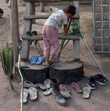 A child climbs around a display of shoes. One boot is centered.